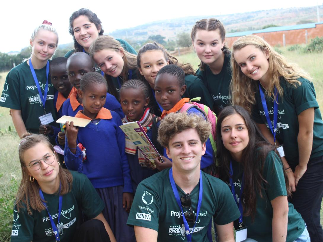 Teens take a photo with Kenyan children after a medical outreach at a school as part of a service learning trip for high school students